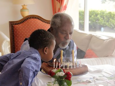 Kofi Annan blows out the candles on his 80th birthday, with help from his grandson Atta