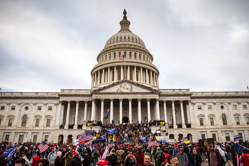 A large group of pro-Trump protesters stand on the East steps of the Capitol Building after storming its grounds on January 6, 2021 in Washington, DC.Alex Gakos / Shutterstock.com